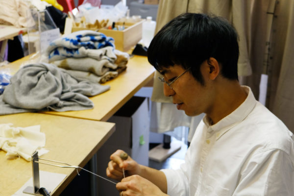 """Hiroyuki Murase, founder and designer of the """"Suzusan"""" label is sitting at a table and knotting a thread."""