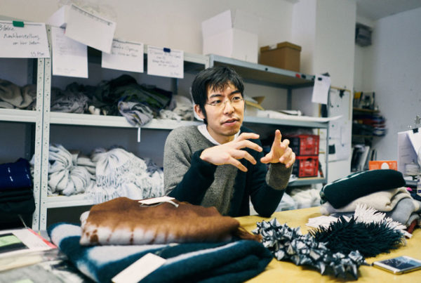 """Hiroyuki Murase, founder and designer of the """"Suzusan"""" label, sits at a table and gesticulates with his hands while speaking. Various items of clothing from the label are on the table."""
