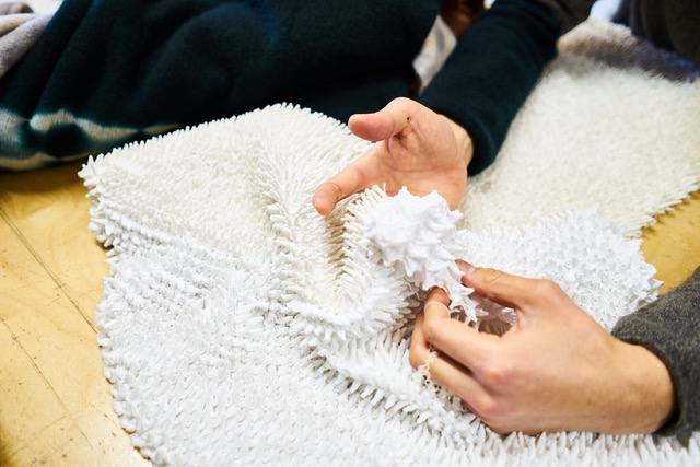 """Hiroyuki Murase, founder and designer of the """"Suzusan"""" label, is holding a white fabric that looks like it has thorns."""