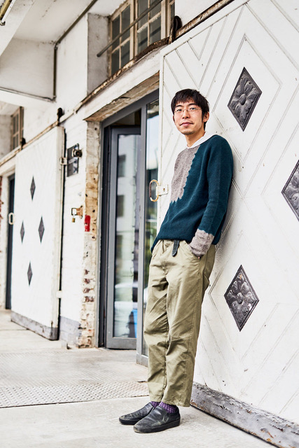 """Hiroyuki Murase, founder and designer of the """"Suzusan"""" label, leans against a wall outside of his studio."""