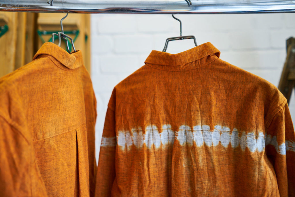 """Orange shirts of the label """"Suzusan"""" hang on a stand."""