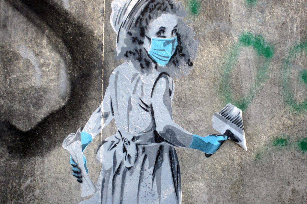 Artwork by the artist seiLeise: A girl with a mask and gloves holds a paste brush and paper in her hand.