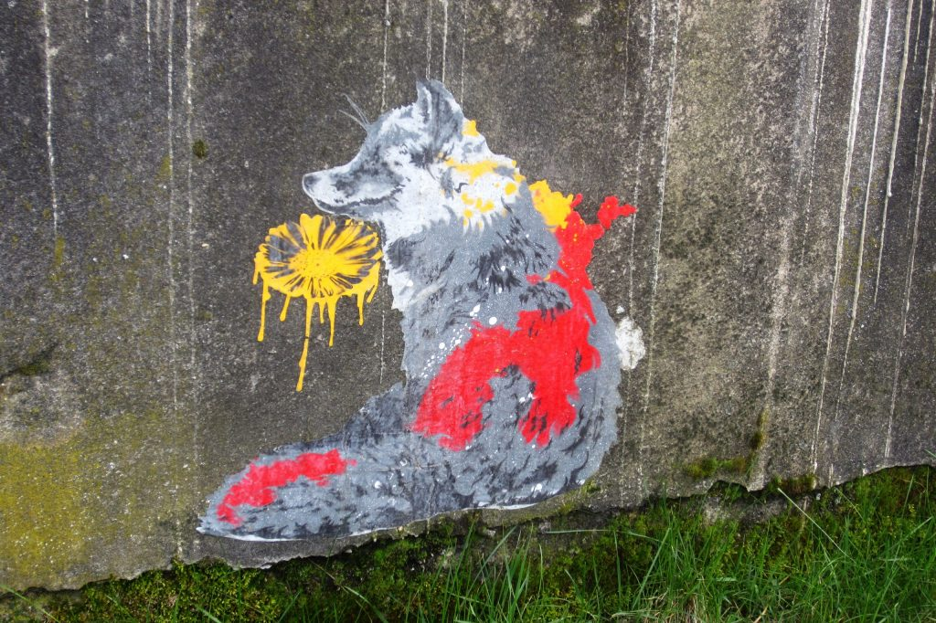 Artwork by the artist seiLeise: A fox surrounded by yellow and red sprinkles sniffs a yellow flower.