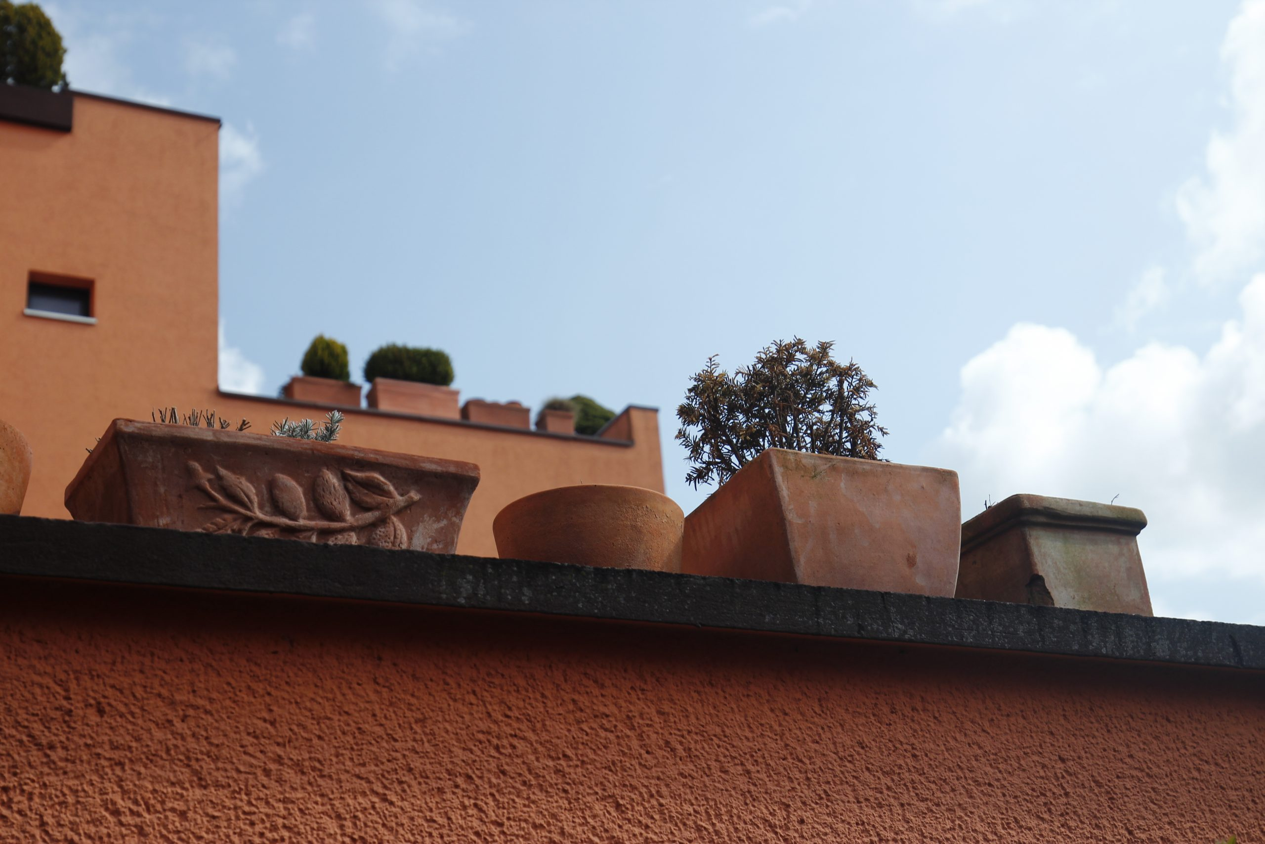 """Terracotta flower potts stand on a wall. The """"Finnstadt"""" settlement complex in Dorsten can be seen in the background."""