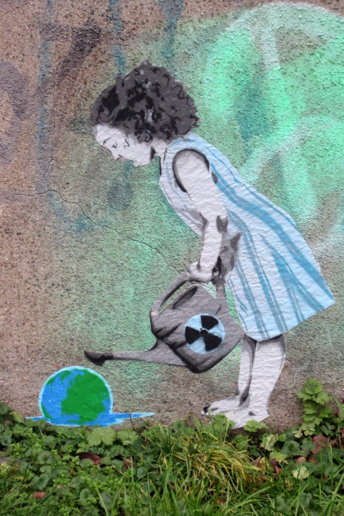 Artwork by the artist seiLeise: A girl in a blue-striped dress holds a watering can with an atom symbol on it. A melting earth lies in front of her.