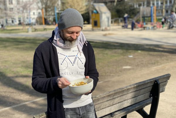A man with a beard and a hat holds a VYTAL bowl with cereal and fruit in it.