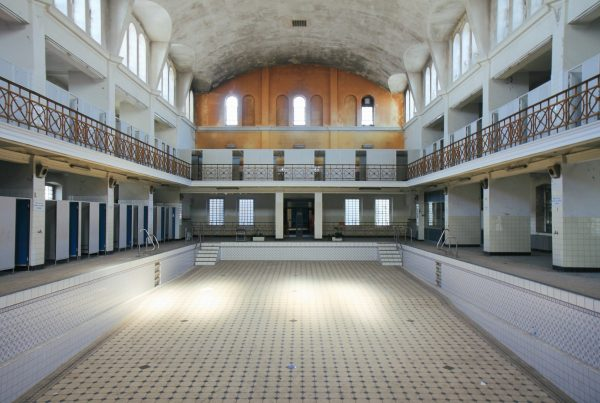Interior of the Stadtbad Krefeld. You can see the empty main pool in the middle of the building. Changing rooms can be seen around the outside.