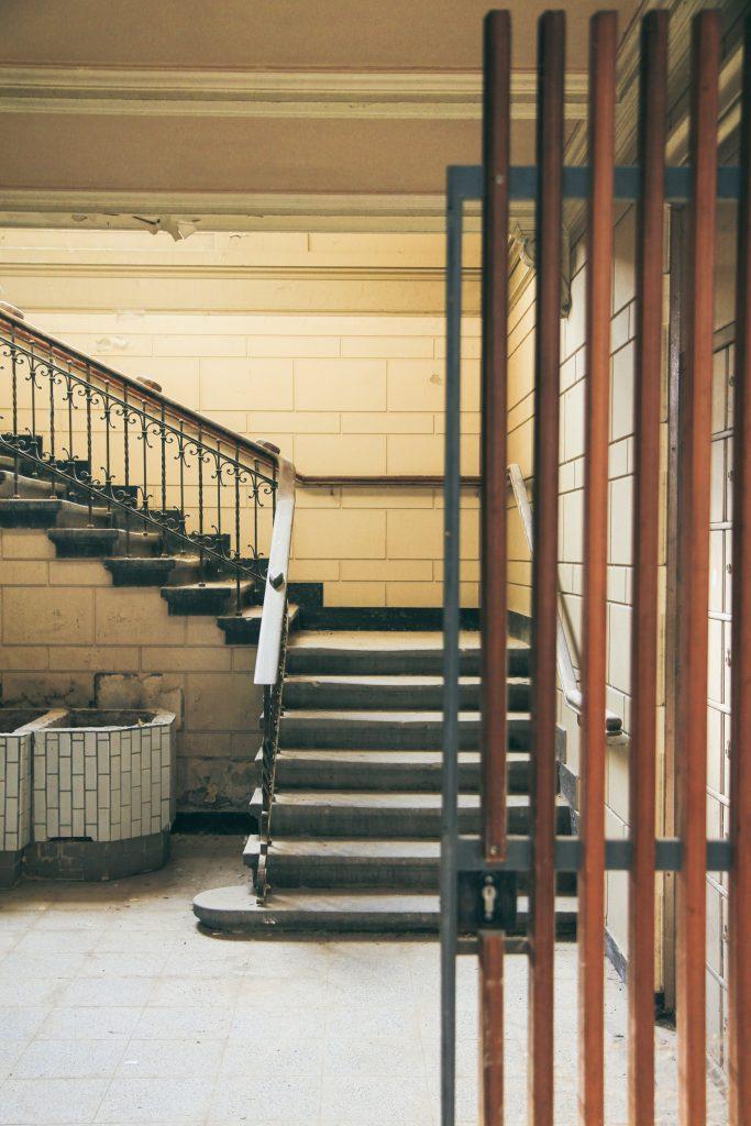 Innenbereich des Stadtbad Krefeld. Man sieht eine Treppe mit verziertem Geländer. Der Eingang wird halb von einer Gittertür blockiert.