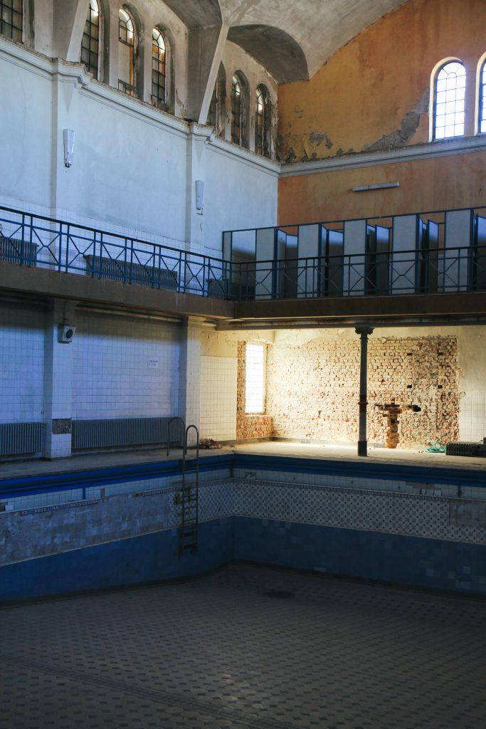 Innenbereich des Stadtbad Krefeld. Man sieht einen leeren Pool und eine Wand, an der das Mauerwerk offen steht.