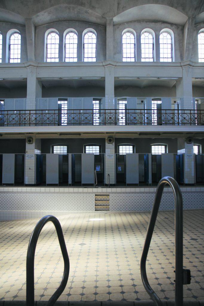 Innenbereich des Stadtbad Krefeld. Man sieht einen leeren Pool und Umkleidekabinen mit offenen Türen.