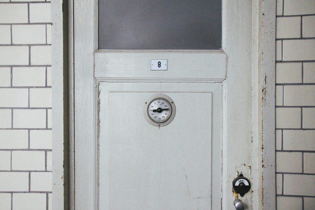 Innenbereich des Stadtbad Krefeld. Man sieht eine Tür mit Fenster und eingebautem Thermostat. Das Holz ist leicht verzogen und die Farbe blättert von der Tür ab.