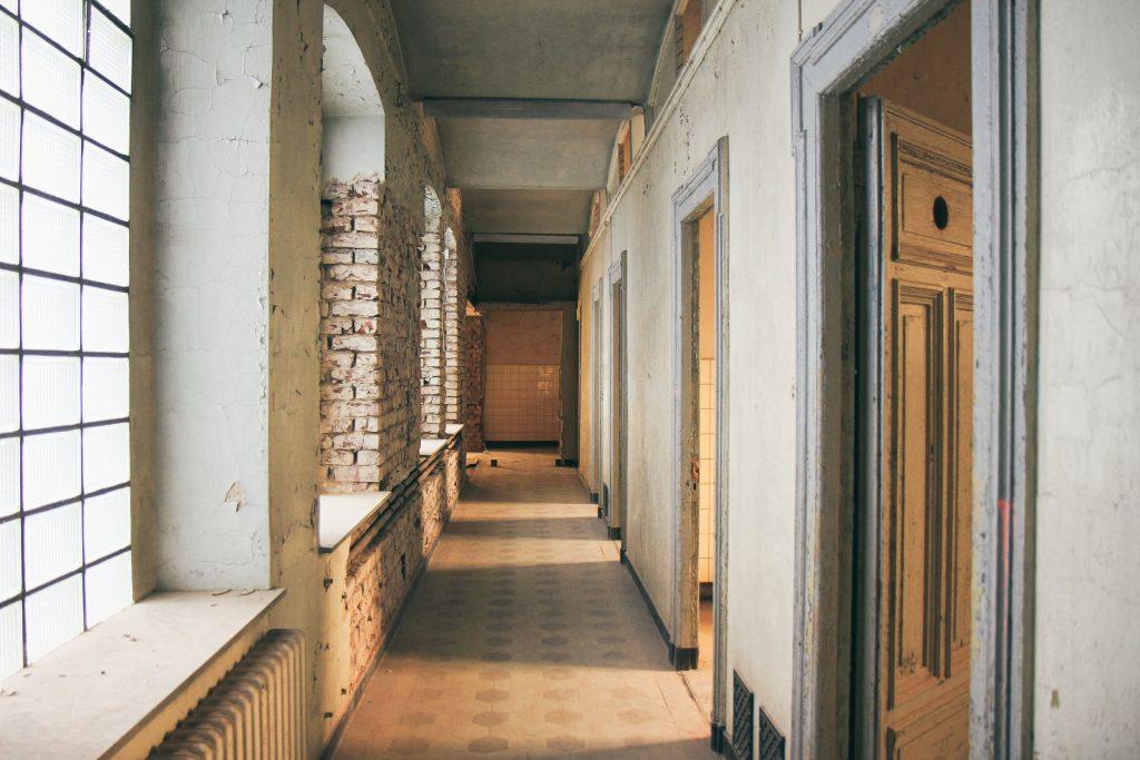 Innenbereich des Stadtbad Krefeld. Man sieht einen Flur mit offenen Türen und Holzfußboden. Das Mauerwerk ist teilweise offen zu sehen und die Wandfarbe bröckelt.