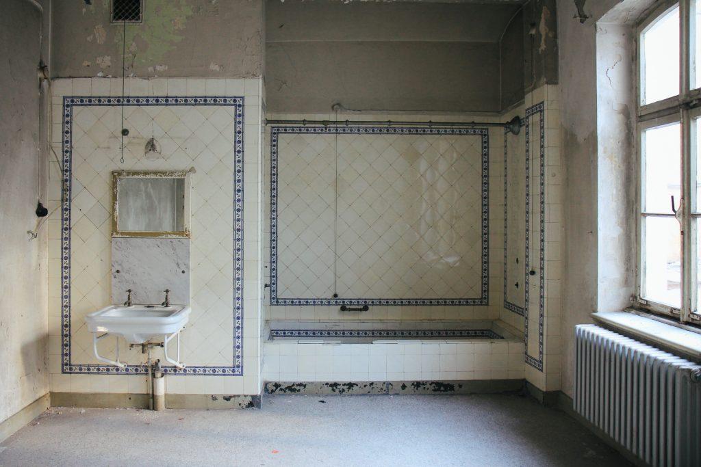 """Innenbereich des Stadtbad Krefeld. Man sieht das """"Kaiserbad"""" mit Waschbecken und Badebereich. Die Fließen bröckeln und überall ist Rost zu erkennen."""