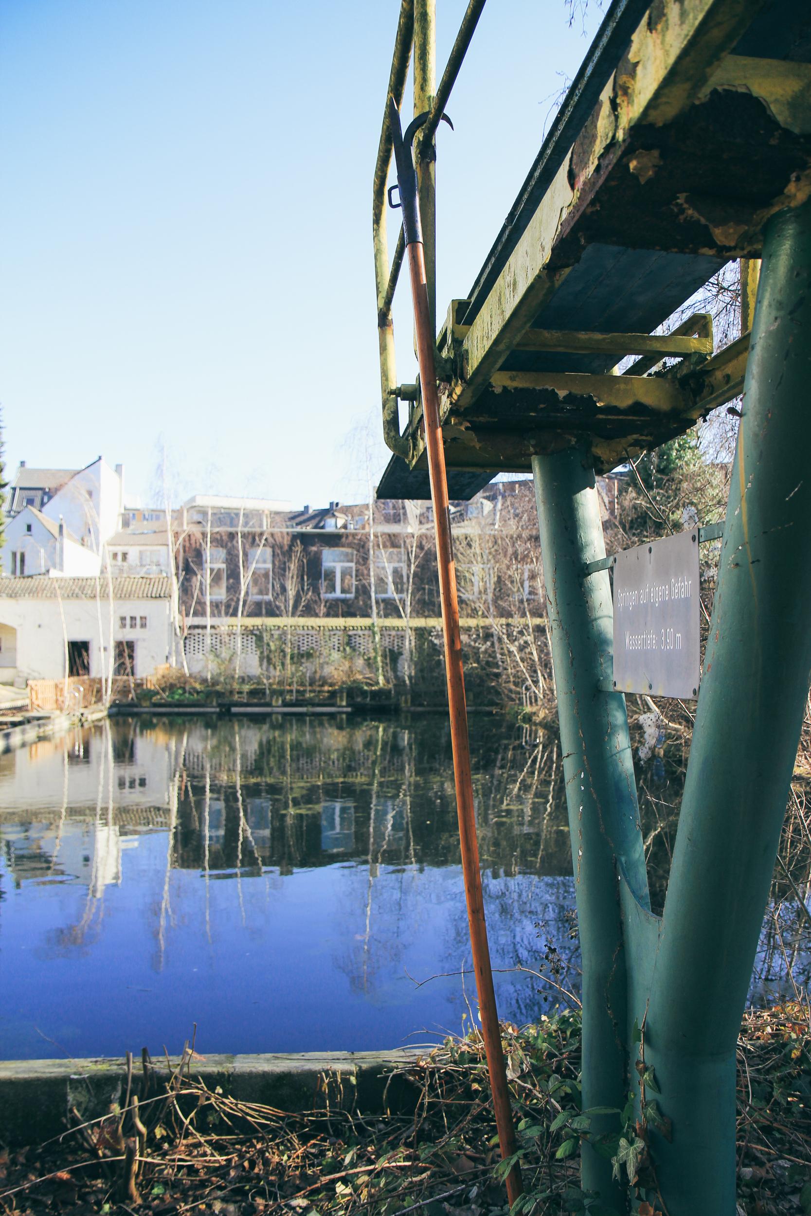 Außenbereich des Stadtbad Krefeld. Man sieht einen alten Sprungturm neben einem Becken.