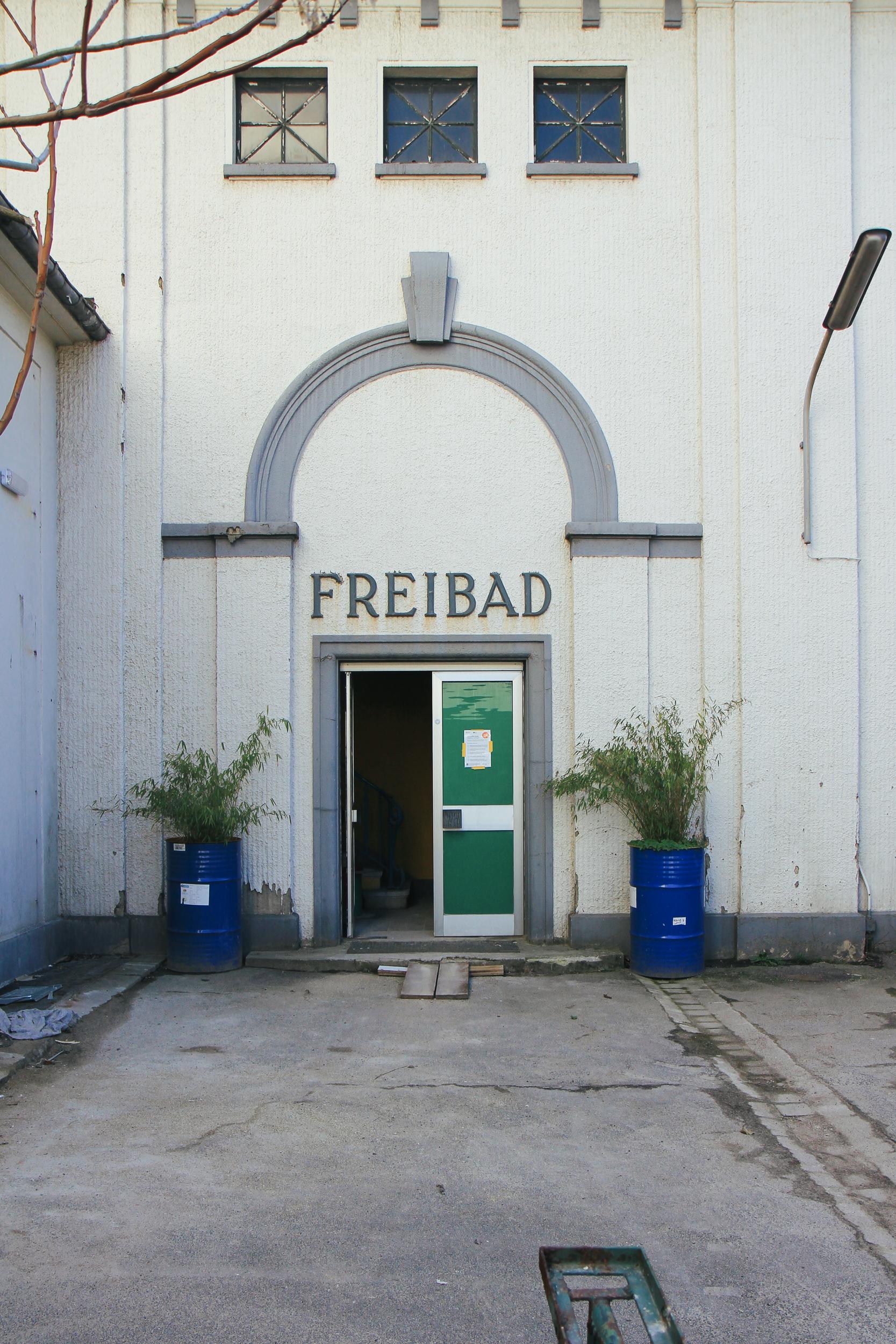 """Außenansicht der Fassade des Stadtbad Krefeld. Man sieht den Eingang, über dem """"Freibad"""" steht. Neben der Tür stehen Fäßer mit Grünpflanzen."""