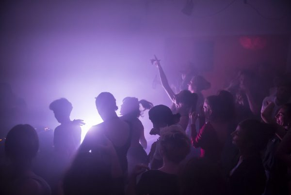 People dance in purple lights and fog.