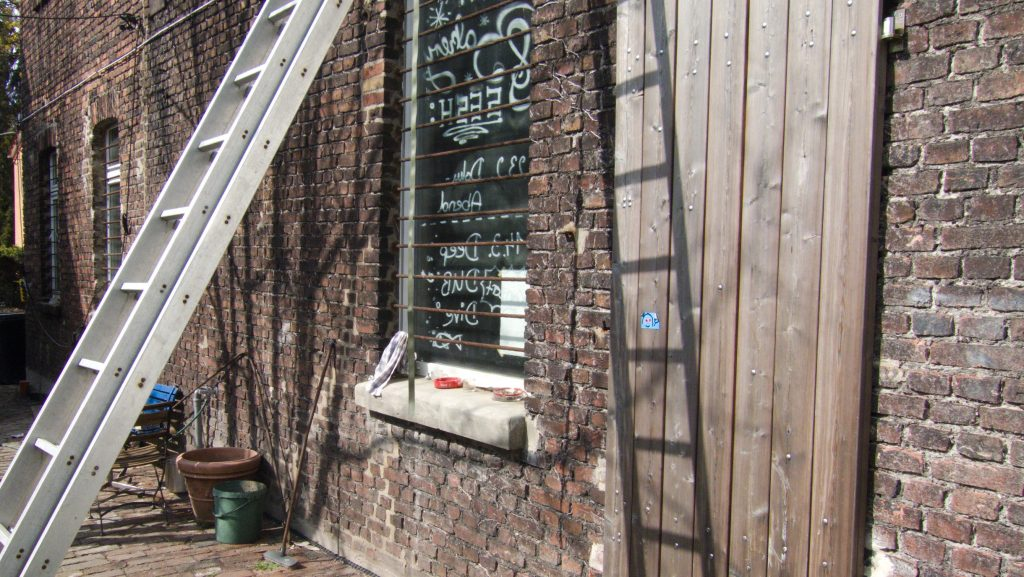 """Outside area of the jazz cellar """"Bakery"""" in Bochum. You can see a metal ladder leaning against a house wall."""